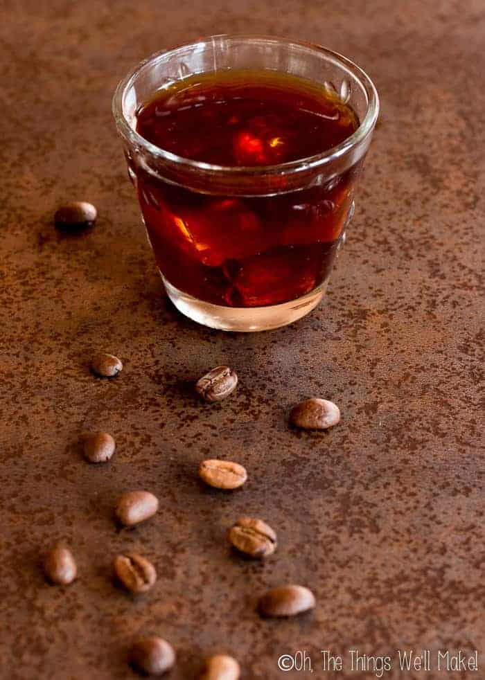 a glass of cold brew coffee with ice surrounded by coffee beans