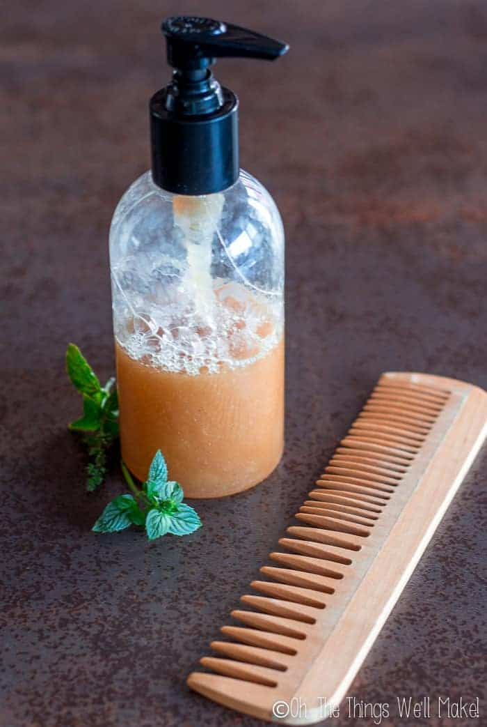 A homemade peppermint clarifying shampoo in a pump bottle next to peppermint sprigs and a wooden comb