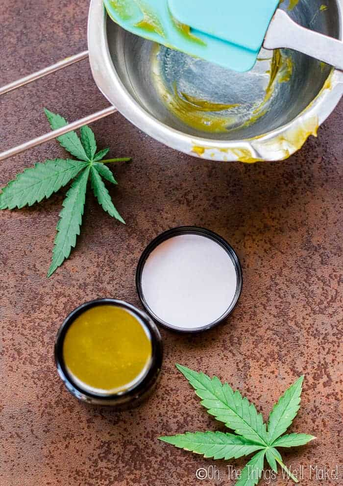 A homemade CBD salve on a countertop with a double boiler insert and a spatula that are covered with