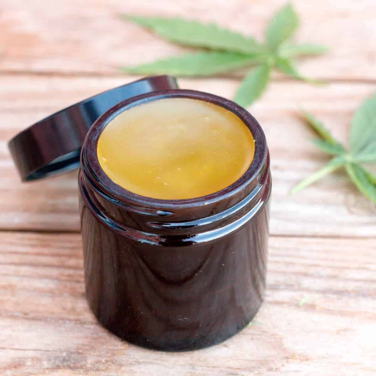 An amber colored glass jar filled with a homemade CBD salve.
