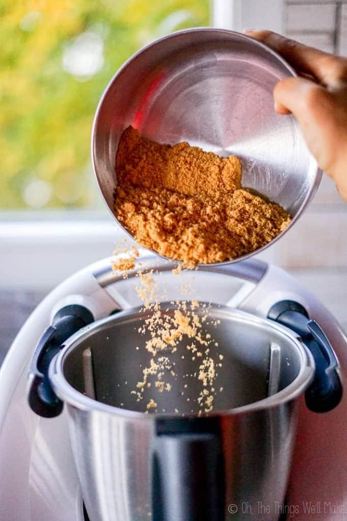 Pouring organic demerara sugar into a food processor.