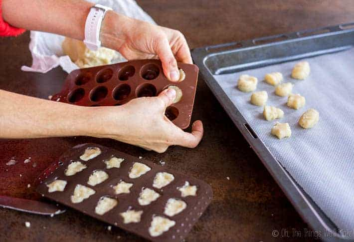 pressing the marzipan dough into candy molds to shape them.