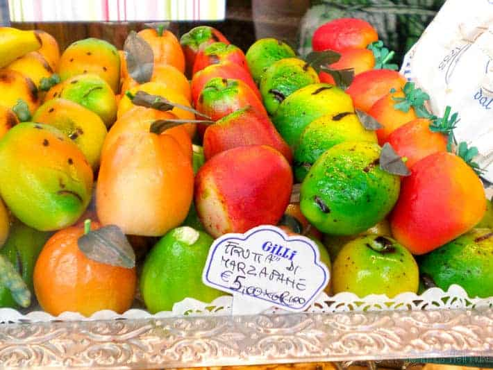 Two layers of multi-colored marzipan fruit figures in a store window in Italy.