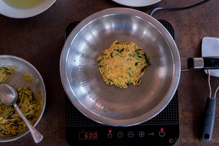 A zucchini pancake (hobakjeon) being fried in a stainless steel frying pan.