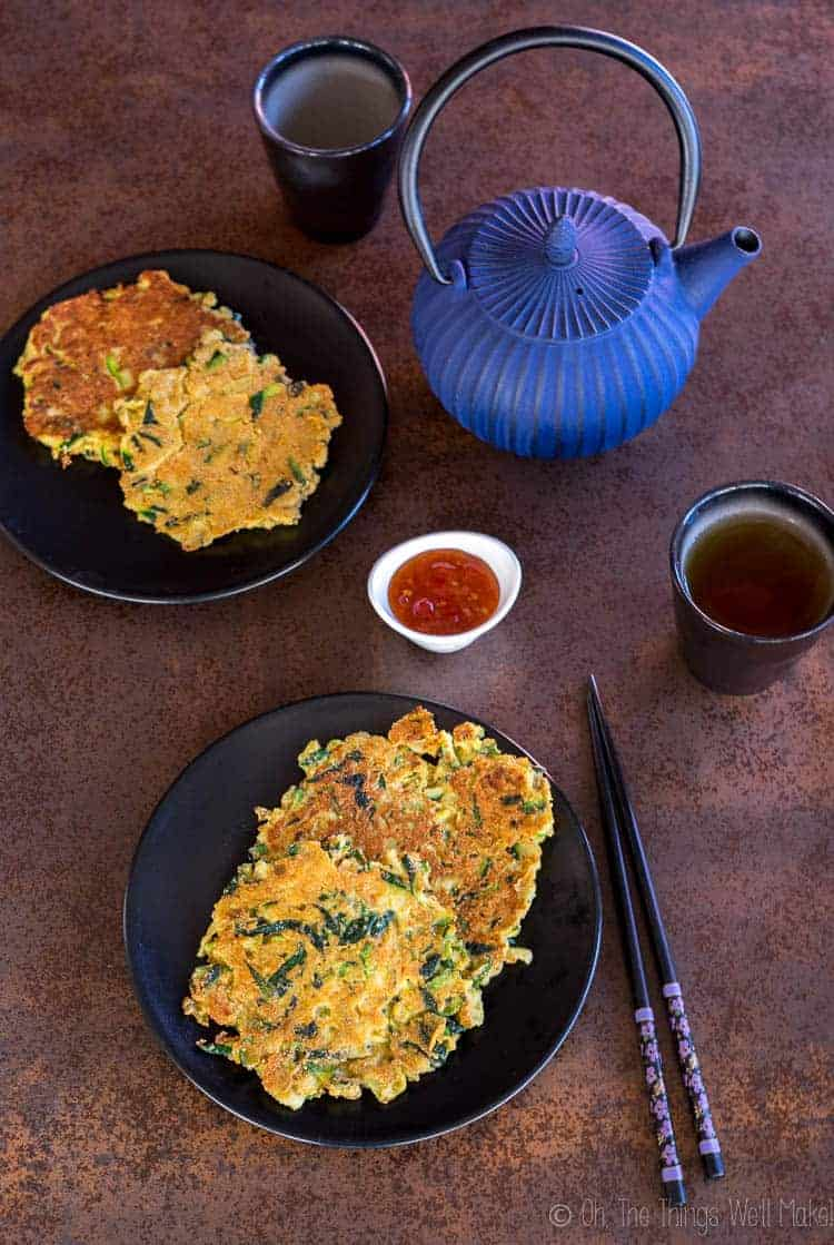 Overhead view of 4 zucchini pancakes, or hobakjeon, with some sweet and sour sauce.