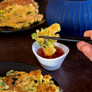 dipping a piece of zucchini pancakes (hobakjeon) into sweet and sour sauce with chopsticks.