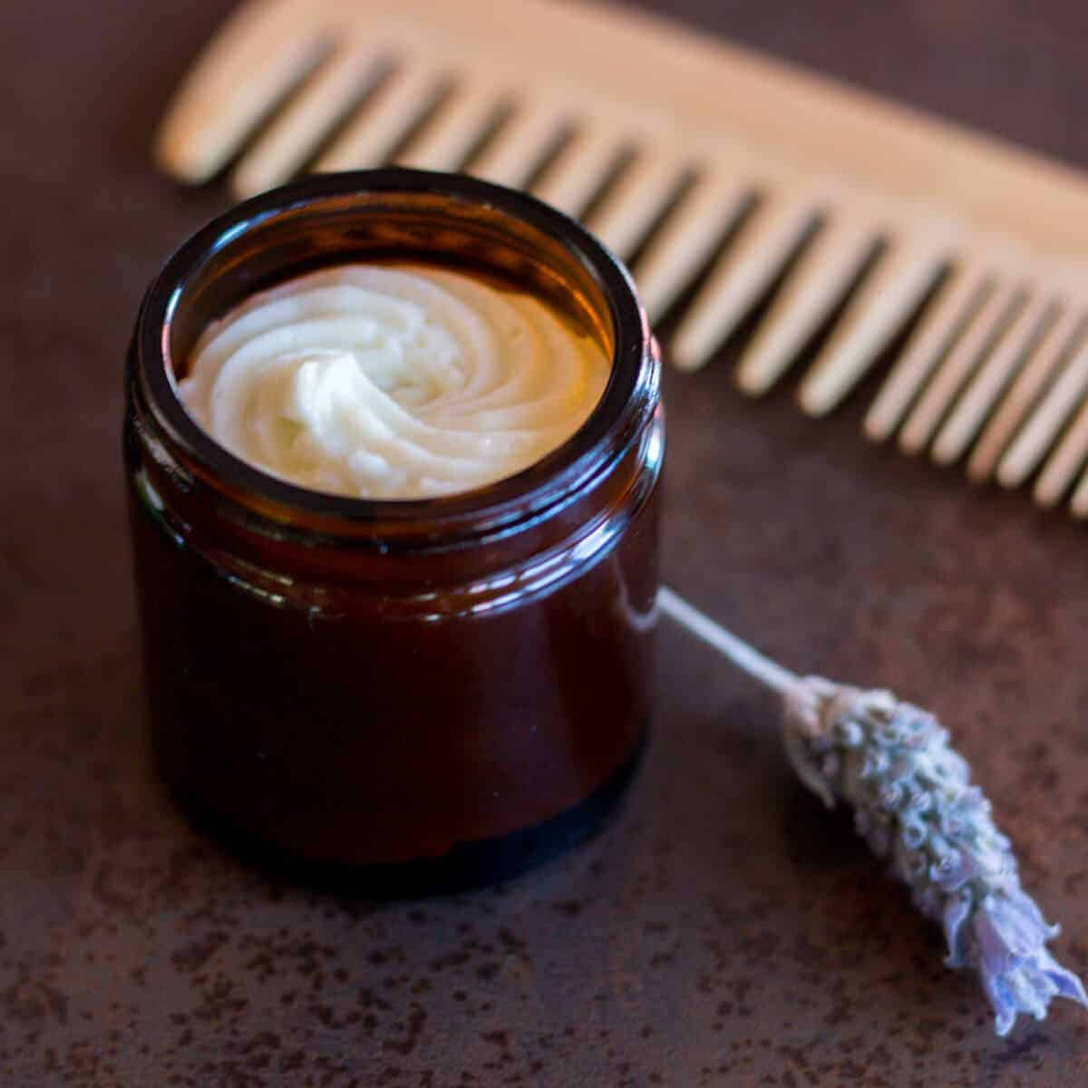A jar filled with a homemade hair butter next to a sprig of lavender and a wooden comb