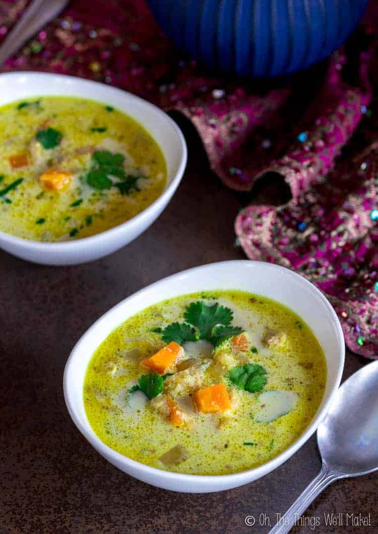 Closeup of a bowl of chicken Mulligatawny soup with visible carrots and cilantro garnish.