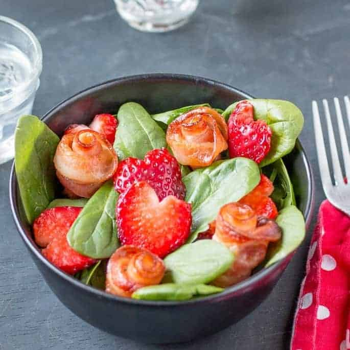 A salad with bacon roses and strawberry hearts