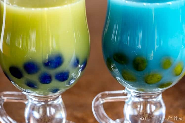 closeup of two bubble teas: one green with blue boba and one blue with green boba.