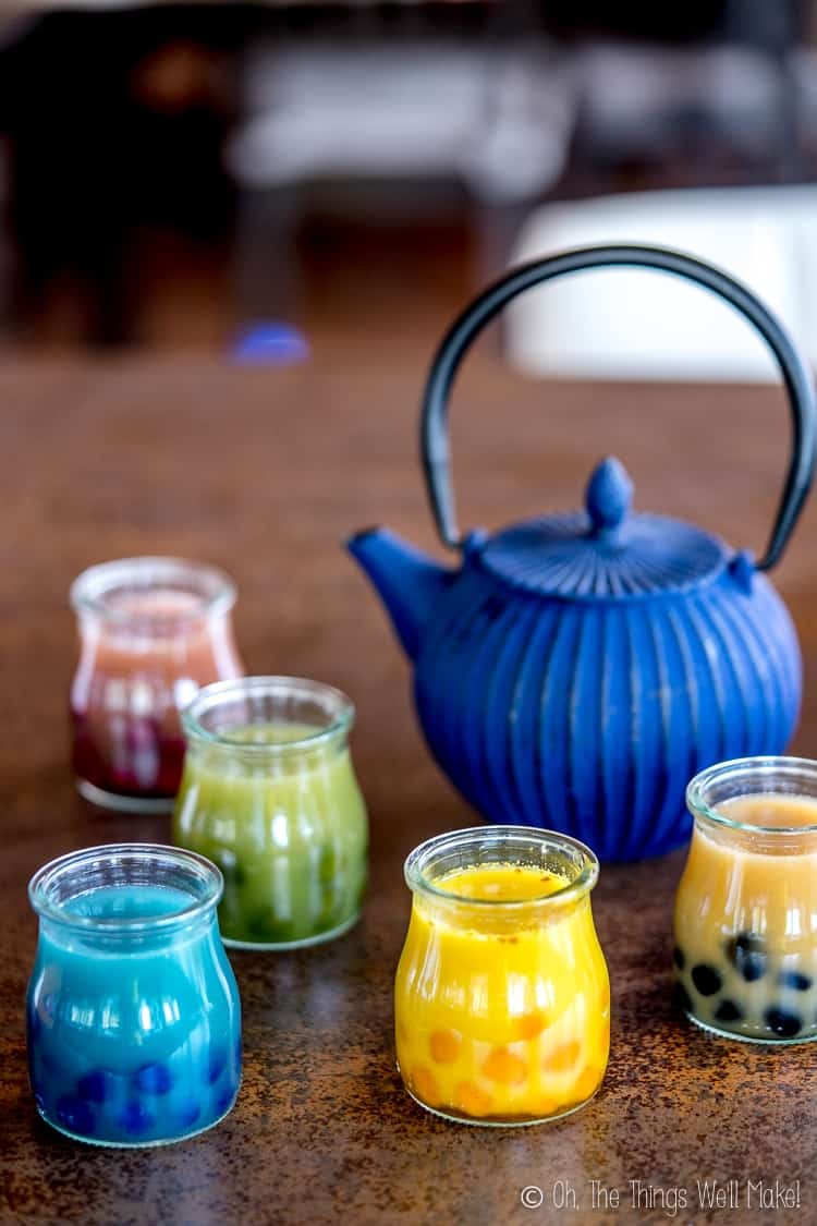 A Blue Teapot shown with five bubble teas made in a variety of natural colors