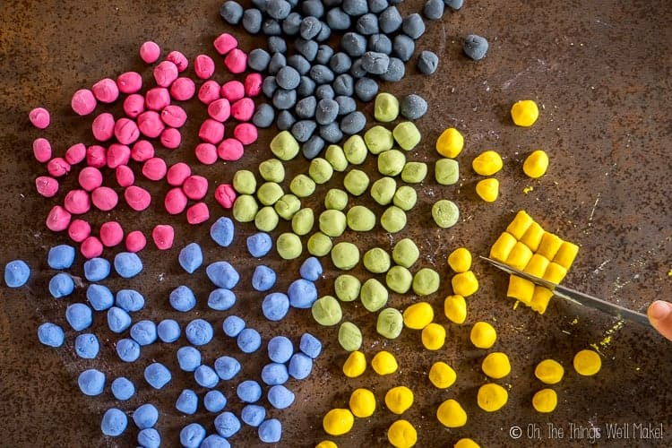 Overhead view of a knife cutting rolls of yellow tapioca dough surrounded by homemade boba already formed in a variety of colors.
