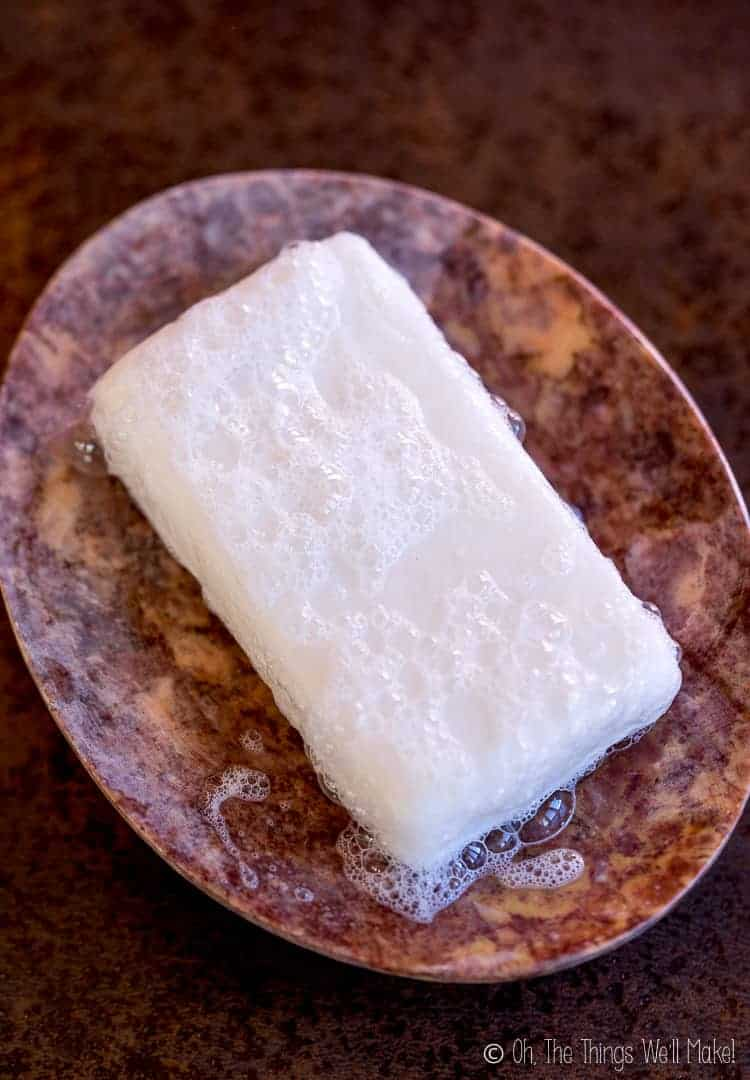 Closeup of a homemade shampoo bar in a stone soap dish.