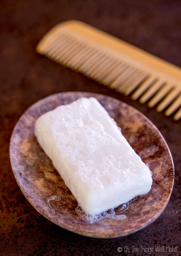 Overhead view of a homemade shampoo bar in a stone soap dish, next to a bamboo comb
