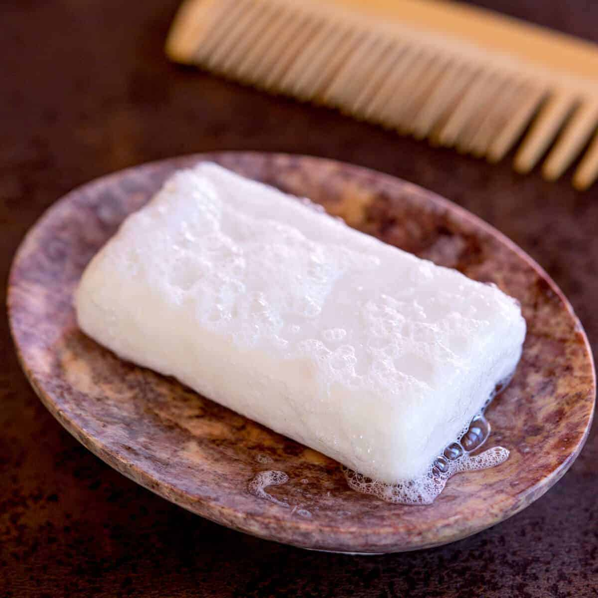 A homemade shampoo bar in a stone soap dish next to a wooden comb