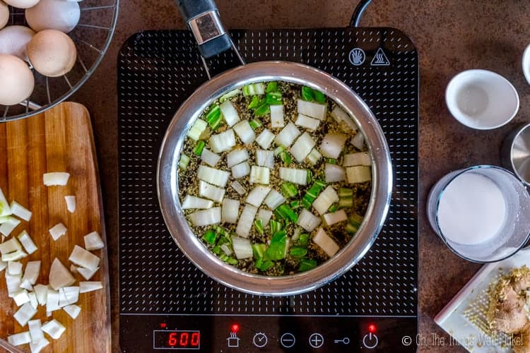 overhead view of chicken broth with bok choi and ginger.