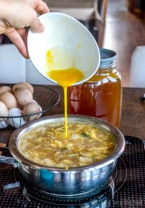 A photo of egg mixture being poured into the soup in a thin stream.