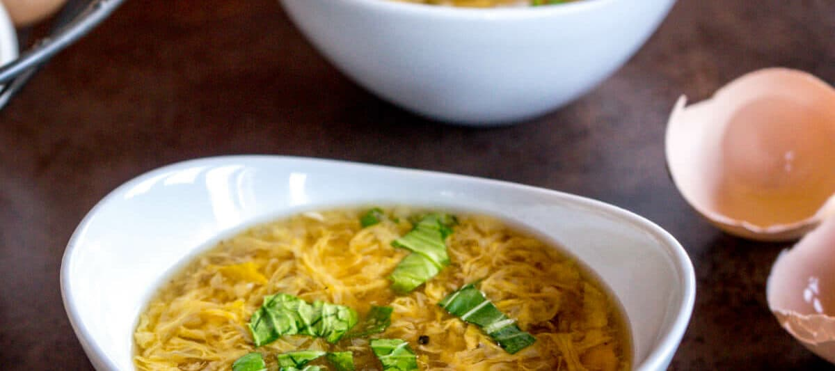 two bowls of egg drop soup with a basket of fresh eggs and open eggshells in the background.
