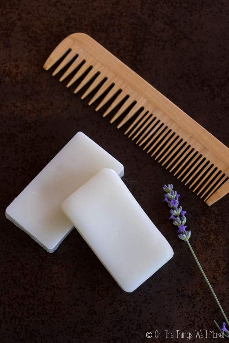 Overhead view of two conditioner bars next to a sprig of lavender and a wooden comb.