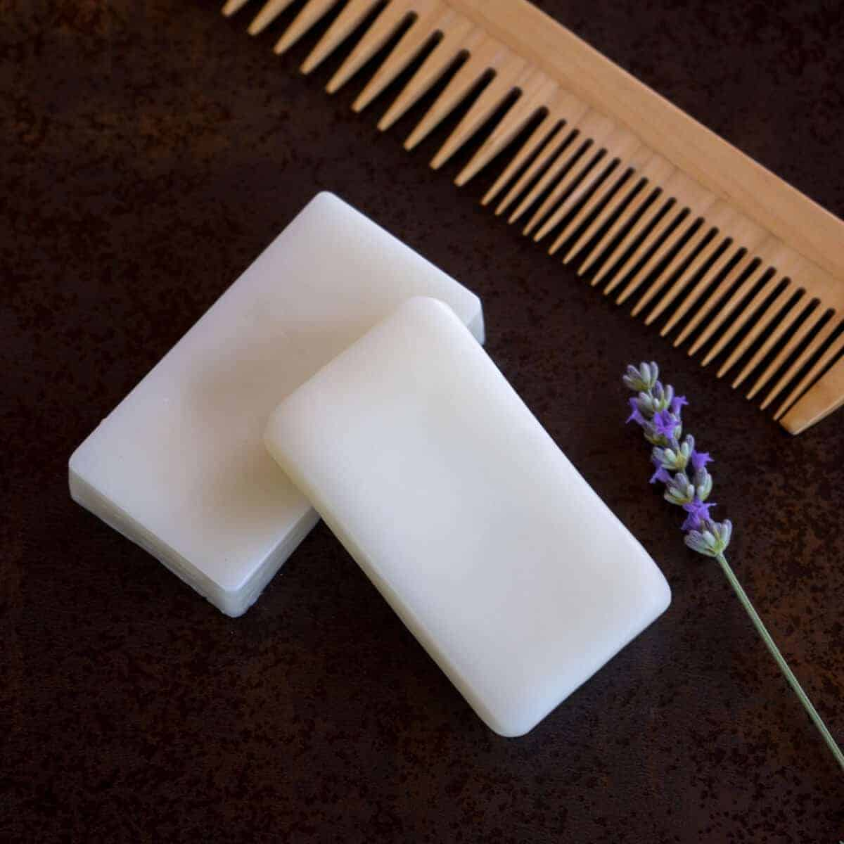 Two homemade conditioner bars on a counter with a sprig of lavender and a wooden comb
