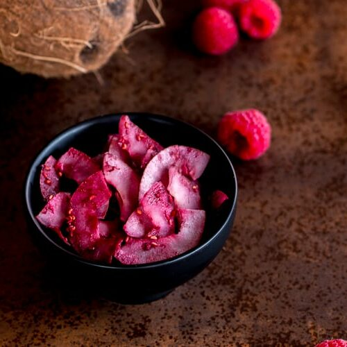 A bowl of raspberry seasoned coconut chips next to fresh raspberries and a coconut