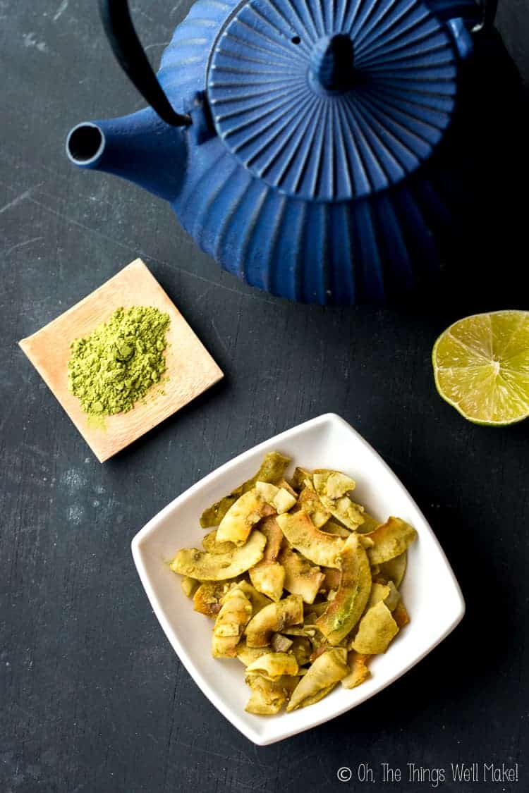 Overhead view of a teapot, matcha, half a lime, and some lime matcha coconut chips