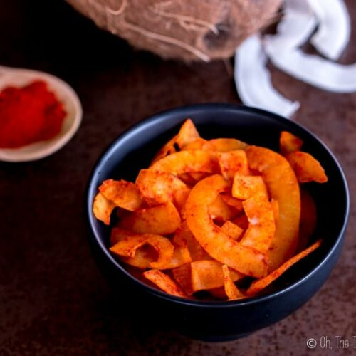 smoked paprika coconut chips in a bowl next to a fresh coconut and a spoonful of smoked paprika.