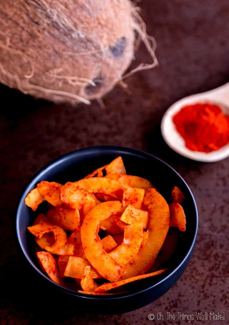 Overhead view of smoked paprika coconut chips with a spoonful of smoked paprika and a fresh coconut
