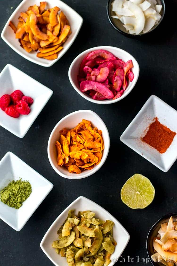 Overhead view of different varieties of seasoned coconut chips with their different flavorings in white bowls.