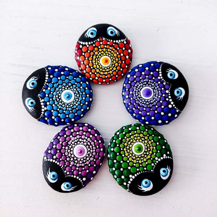 Overhead view of 5 painted rocks with a ladybug mandala design in different colors, placed in a circle.