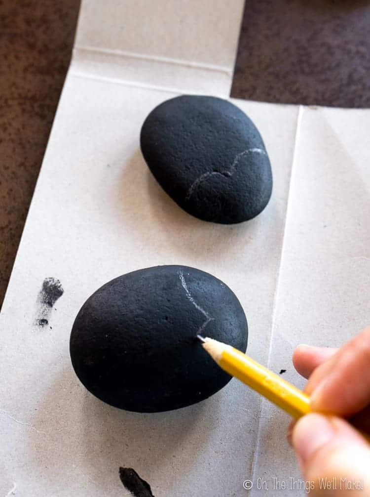 penciling on the design of the ladybug on the black stones.