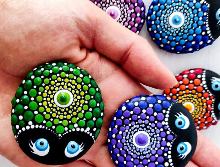 Two ladybug mandala painted stones being displayed on a hand over top of other colorful painted stones.