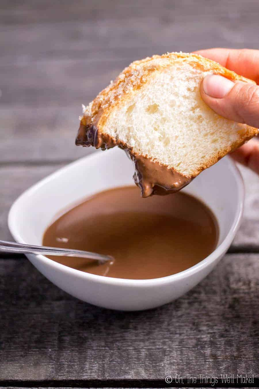 Dipping panquemado into Spanish hot chocolate