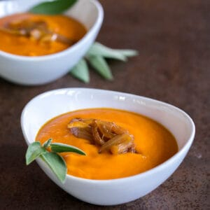 two bowls of a roasted pumpkin soup garnished with fresh sage and caramelized onions.