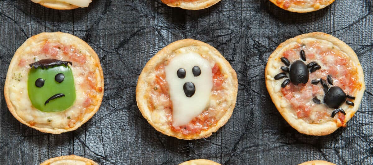 Overhead view of 12 pizzas that have been decorated for Halloween with ghosts, spiders, a bat and other Halloween characters