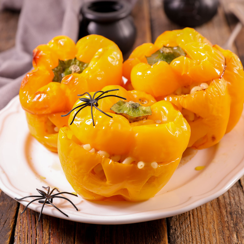 peppers cut into jack-o-lanterns on a plate decorated with plastic spiders