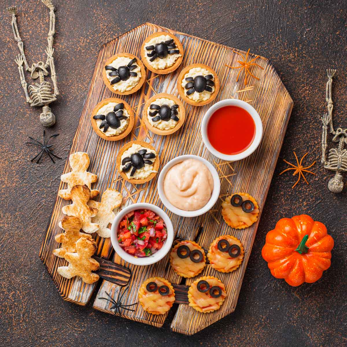 Overhead view of a platter covered with mini mummy pizzas, and tarts covered with olive spiders, amongst other foods.
