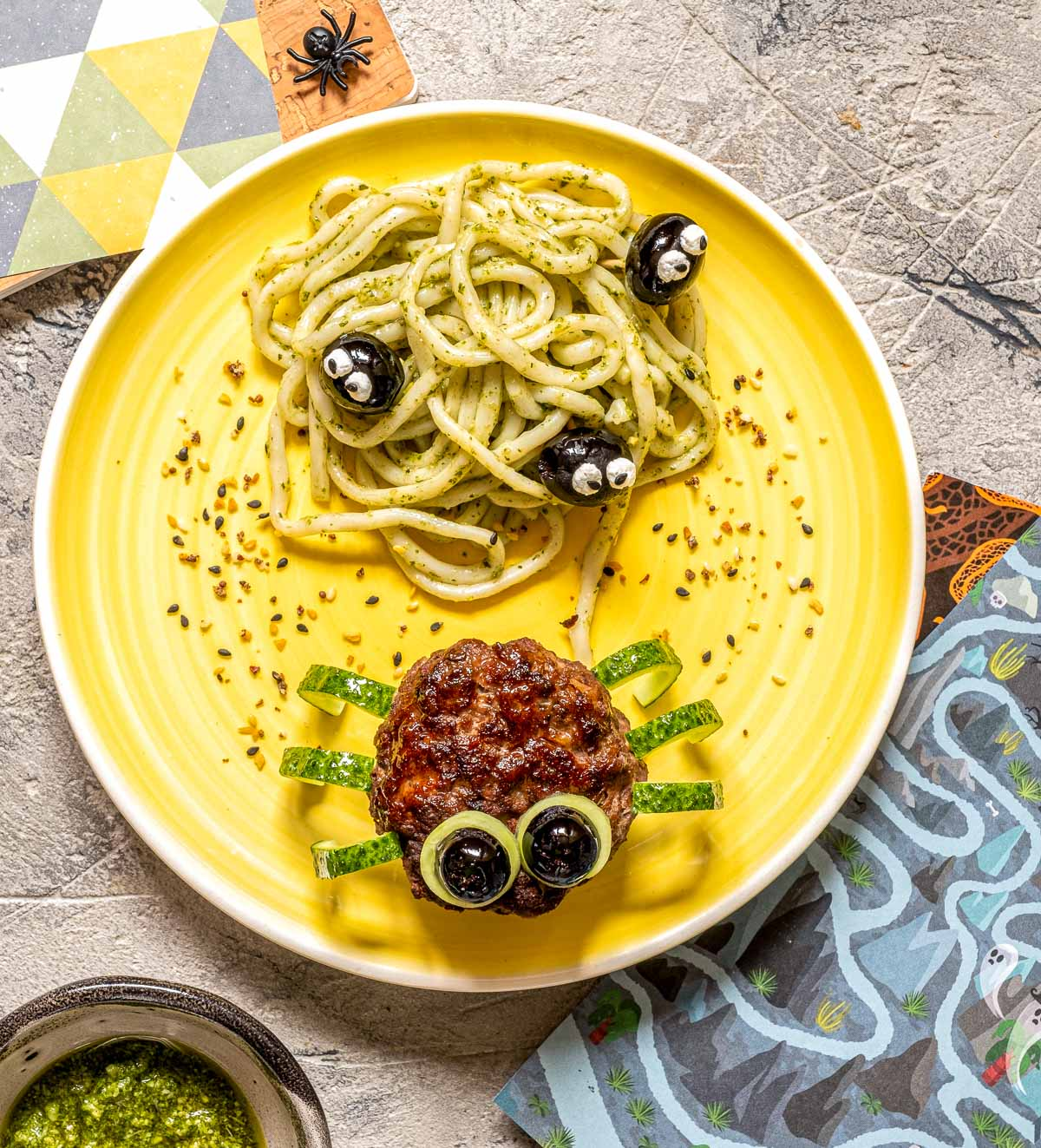 """Overhead view of a plate of spaghetti with pesto sauce (a nest) covered with olives decorated with eyes next to a meatball """"spider"""" with cucumber peel legs"""
