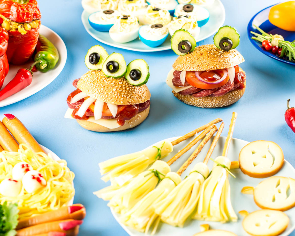 monster hamburgers next to a plate of pretzel and cheese broomsticks, frankfurt witche's fingers, and other Halloween foods.
