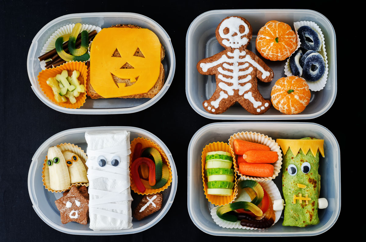 Overhead view of 4 Halloween themed bento boxes with foods decorated with skeletons, monsters, ghosts, pumpkins, and mummies