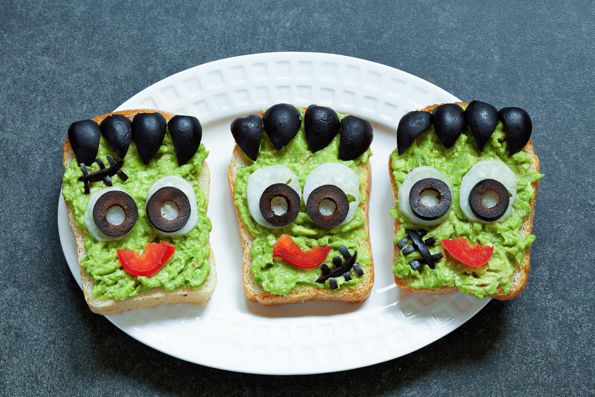3 open-faced avocado sandwiches on a plate with Frankenstein faces made from black olives and red bell peppers.