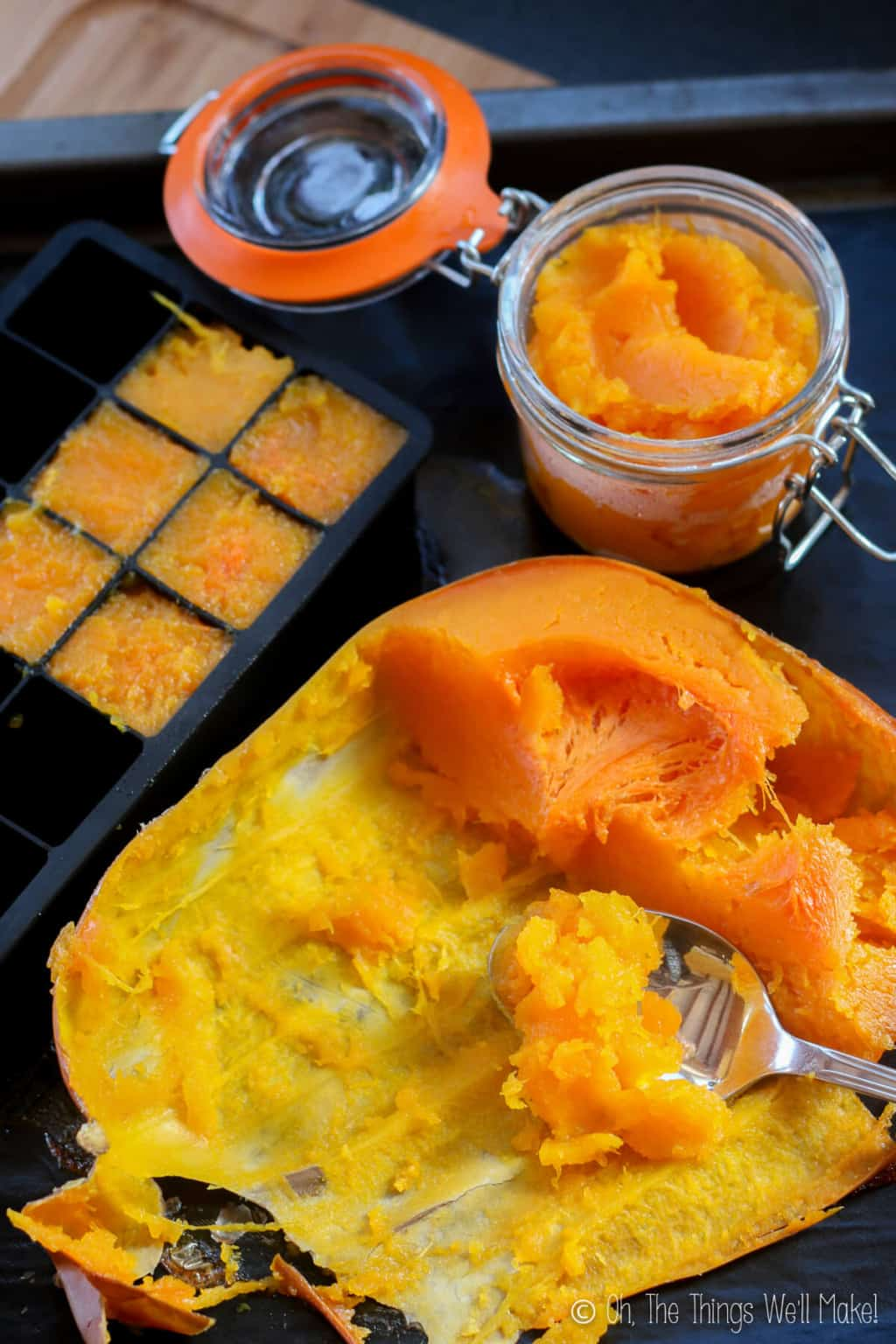 Top view of an orange baked pumpkin below a jar of homemade pumpkin puree and beside a black silicone ice cube tray filled with pumpkin puree for freezing.