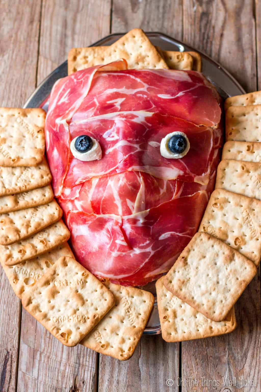 Overhead view of a prosciutto face on a platter, surrounded by crackers.
