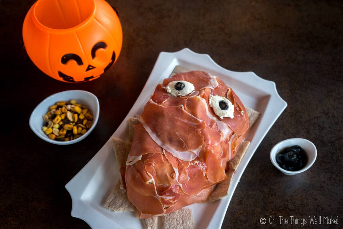 Overhead view of a creepy prosciutto face on a white plate beside a small bowl of nuts and a plastic Jack-o-Lantern.