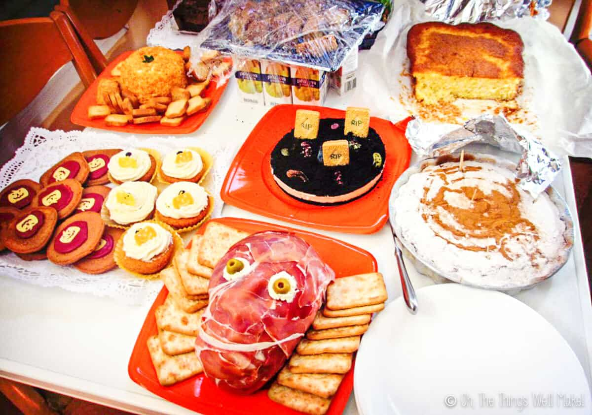 Table with Halloween foods including a prosciuttos face and a pumpkin shaped cheeseball with crackers.