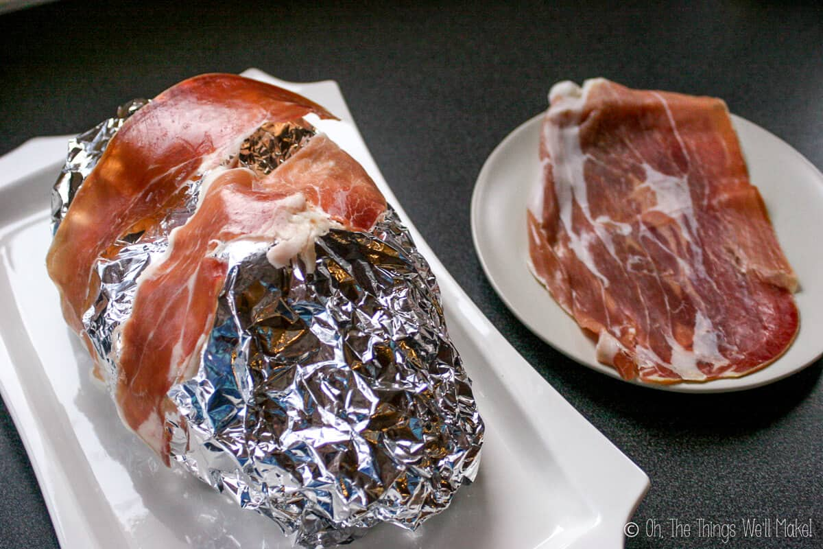 The foil covered face with two slices of prosciutto ham on it, on a white platter with a plate full of prosciutto ham on the side.