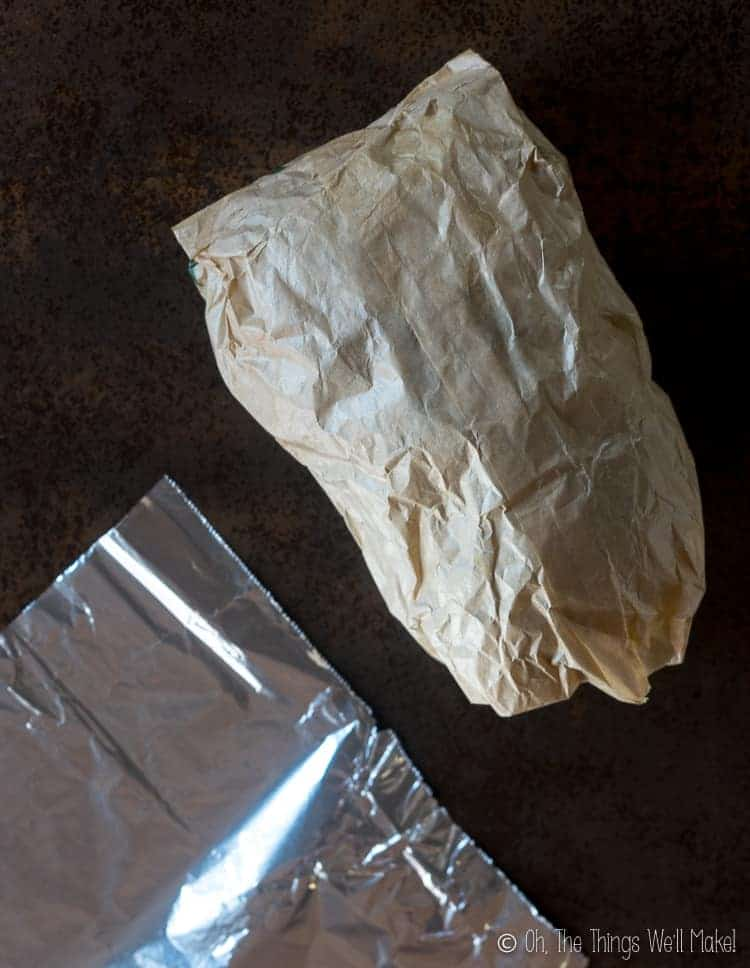 A paper bag filled with paper scraps next to a sheet of aluminum foil.