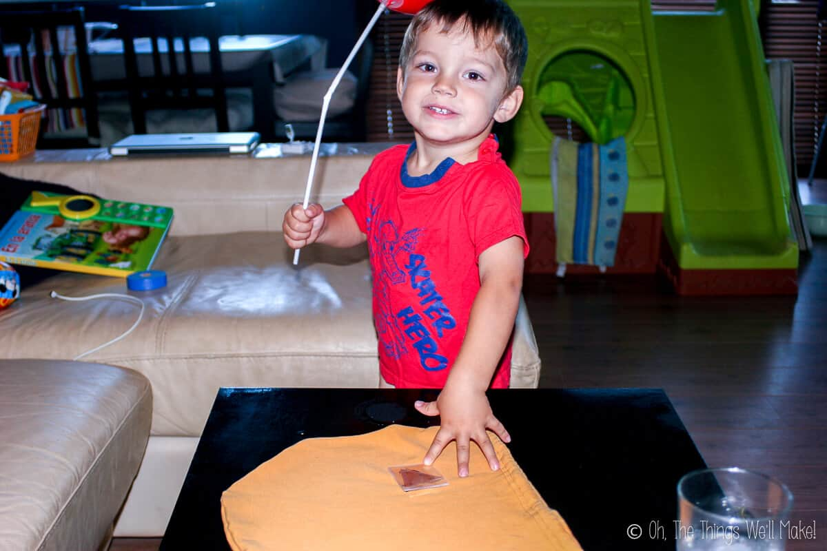 A young boy wearing a red shirt and holding a white balloon stick  eagerly smiling for the camera as he places a hand on an unmade trick-or-treat bag on the table.