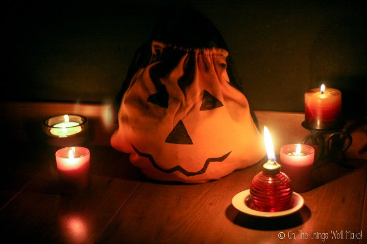A jack-o'-lantern trick-or-treat bag surrounded by lit candles and a small oil lamp.
