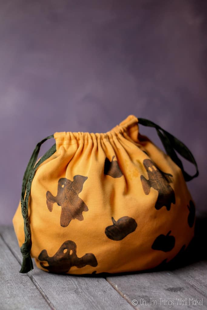An orange handmade trick-or-treat fabric bag decorated with ghosts and bats stamps placed on a grey wood surface and grey photo backdrop.